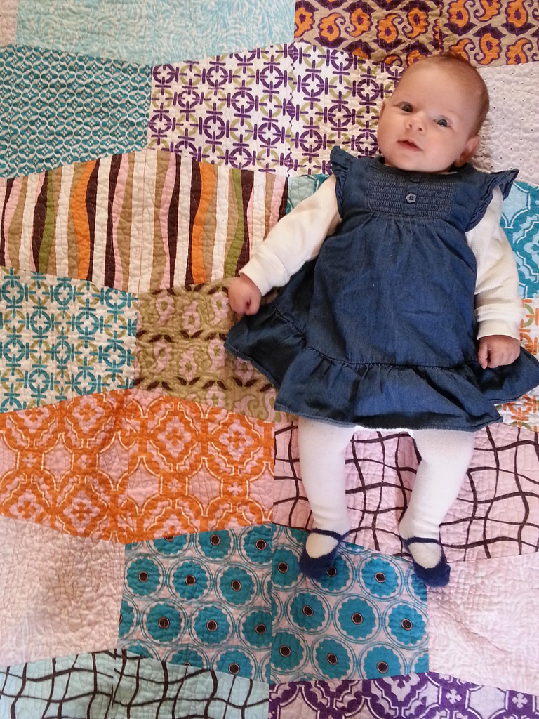 baby laying on a color quilt
